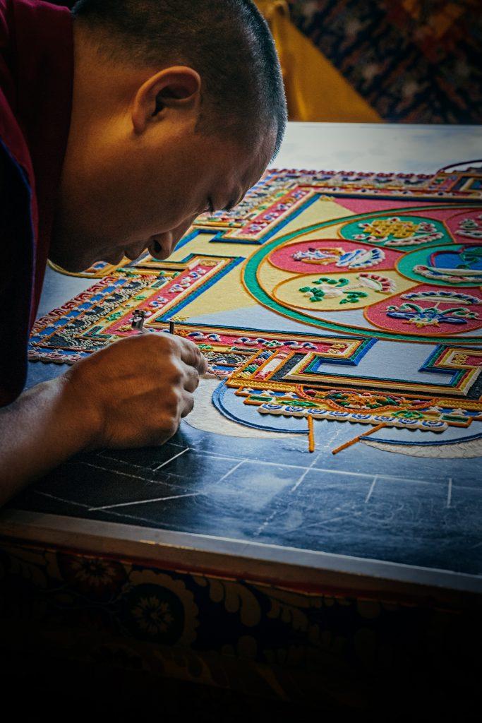 曼荼羅を書く僧侶の写真